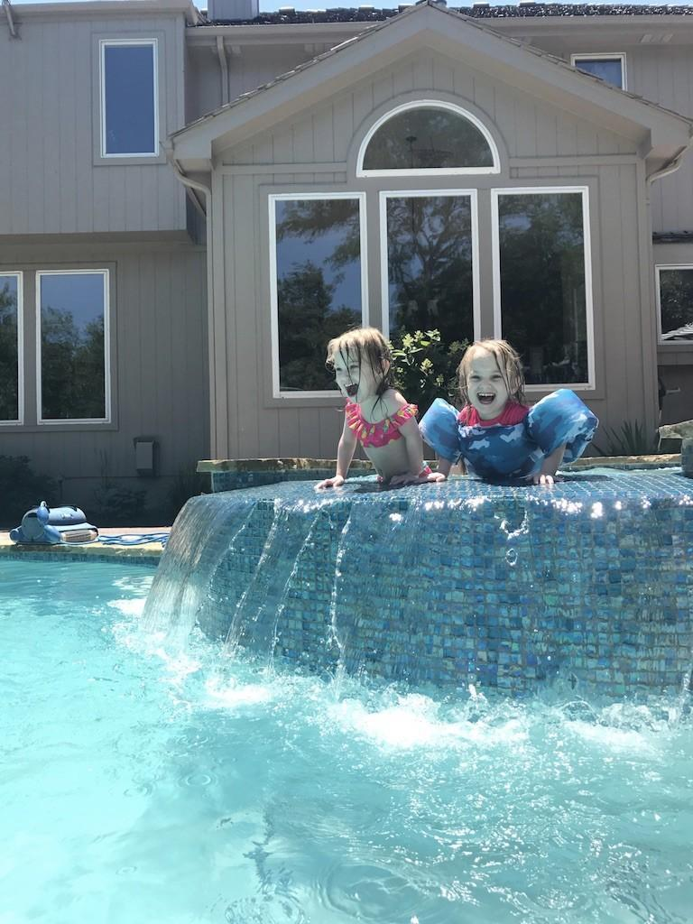 Twin little girls swimming in the pool.