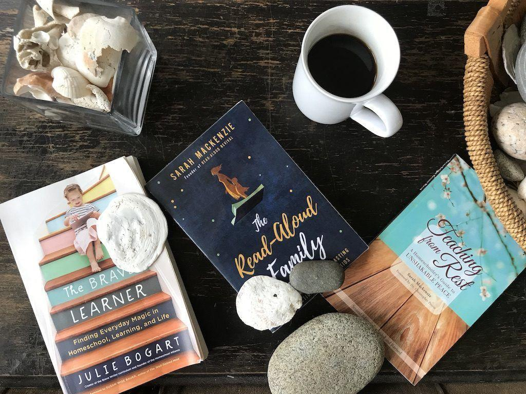 Homeschool Books: The Brave Learner, The Read-Aloud Family, and Teaching From Rest sitting on table with coffee cup