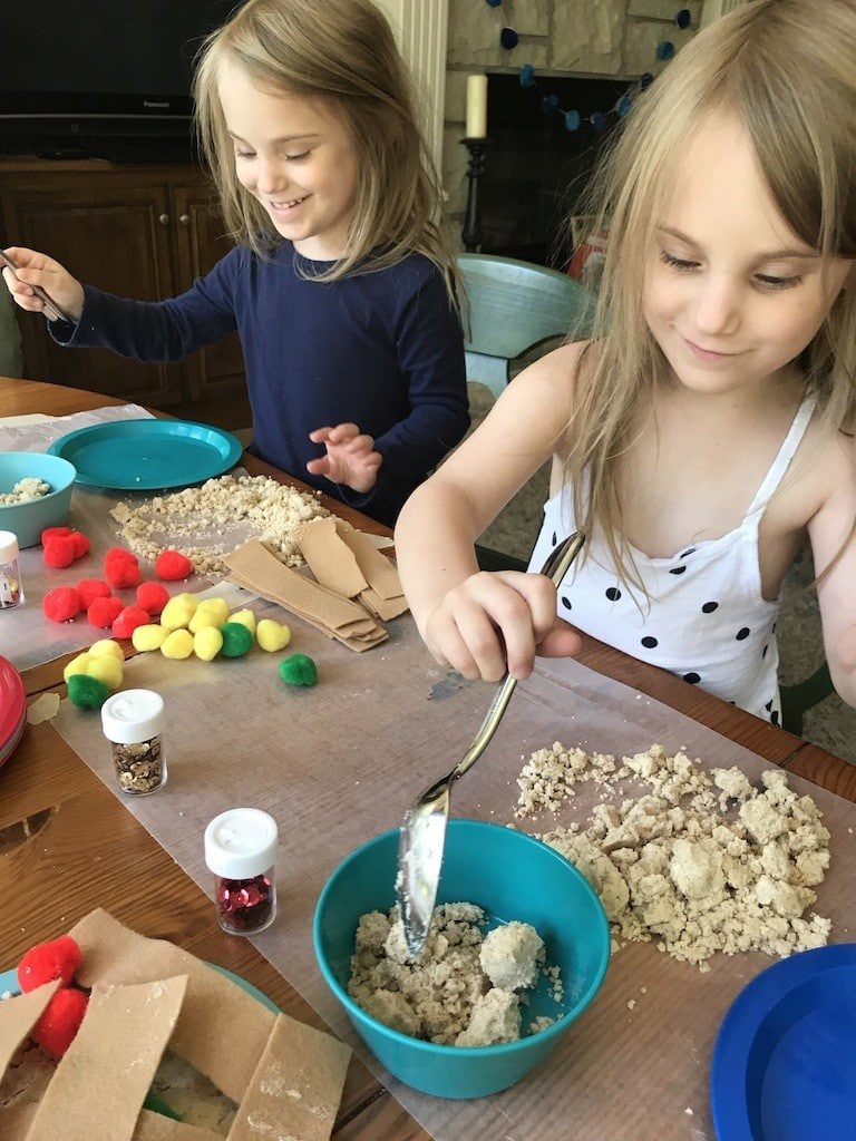 Preschoolers playing with apple cloud dough to make pretend apple pies with felt and pom moms.