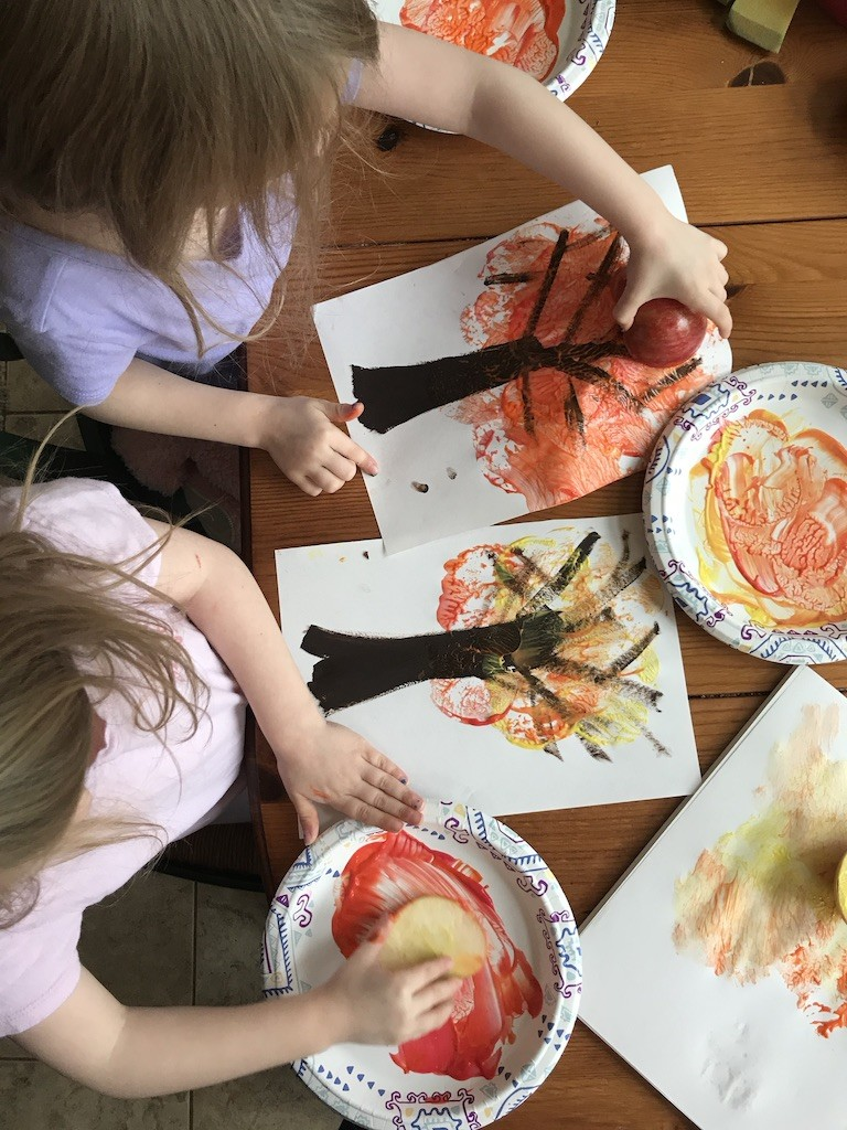 Preschoolers using apples to stamp with paint and create apple trees.